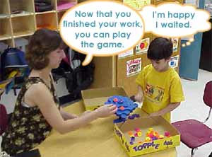 "Teacher and child are playing the game. Teacher says, ""Now that you've finished your work, you  can play the game."" Child thinks, ""I'm happy I waited."""